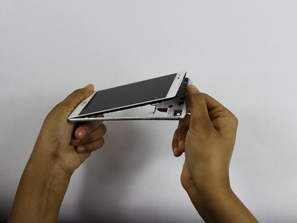 Using your fingers, remove the entire back panel of the phone revealing the internal electronics.