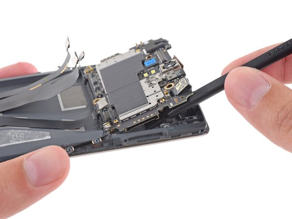 Gently lift the top side of the motherboard and disconnect the antenna to free it from the device.