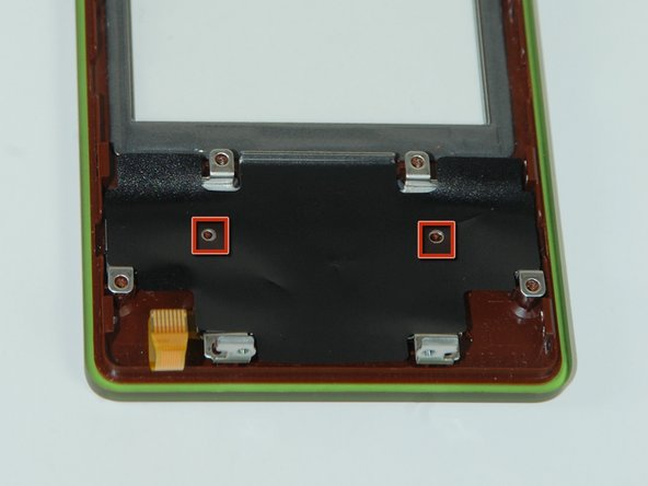 The button assembly is made up of three layers, stacked on two plastic pins protruding from the front plate.