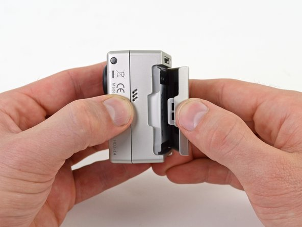 Image 2/2: Gently press down with your thumb and lift the back cover away from the case to remove it.