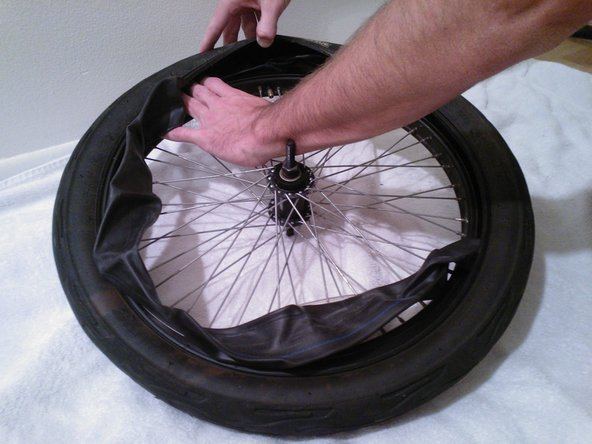If the inner tube has a cap over the nozzle you'll have to remove it before you can pull it out of the rim. Just use your fingers to rotate the cap counterclockwise until it comes off.