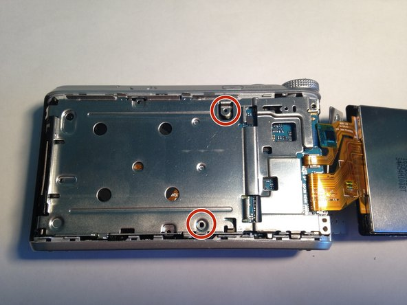 Remove two more 3.2 mm screws on the silver panel using your Phillips #000 Screwdriver.