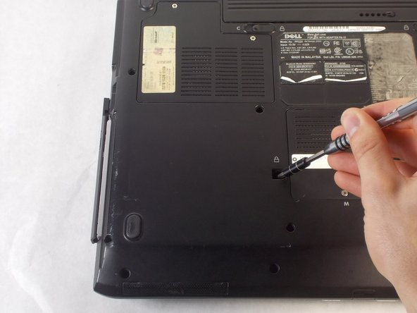 Push the tab to the left until the Optical drive is protruding from the side of the laptop.