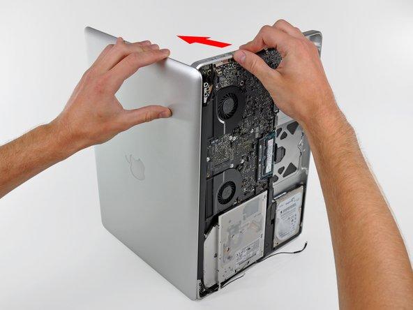 Saisissez le boîtier supérieur de votre main droite et faites-le légèrement pivoter vers le haut de l'écran de sorte que la fixation supérieure de l'écran s'éloigne du bord du boîtier supérieur.