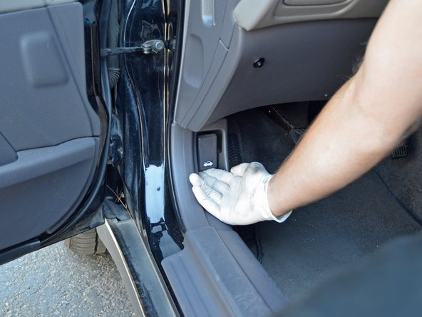 Image 1/3: Locate the hood release latch under the hood. Use one hand to press up on the latch while you lift the hood.