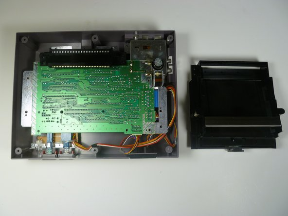 Slide the cartridge tray toward you, away from the 72-PIN connector, and off the motherboard assembly.