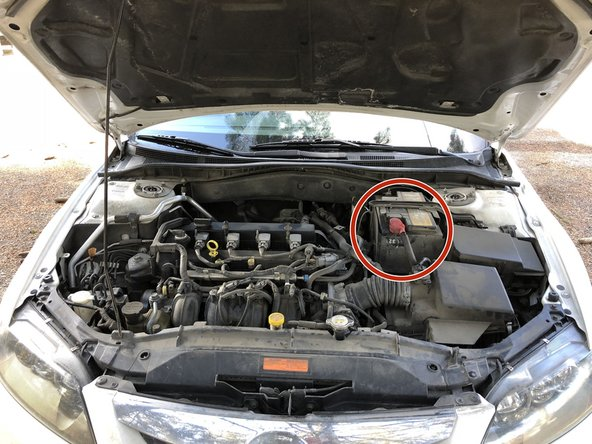 Pop open the hood and locate the battery.