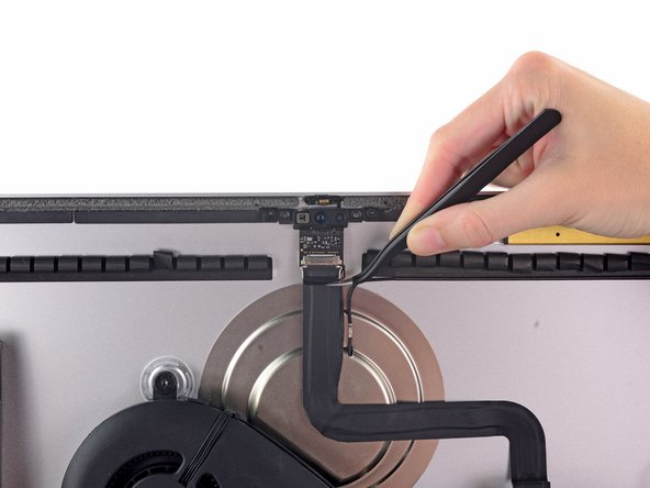 Use a pair of tweezers to grasp and flip the metal retaining bracket downwards to free the iSight camera cable connector.