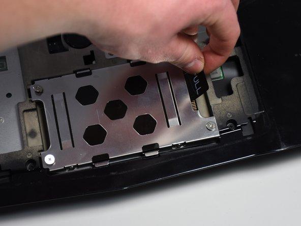 "Once the screws are loosened use the ""PULL"" tab to remove the current hard drive from the computer."