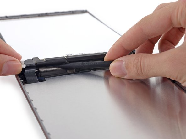 Image 3/3: Push gently between each of the two adhesive tabs; be careful not to damage any of the nearby cables.