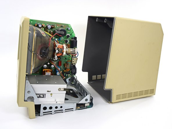 The entire machine slides out of the back case, revealing the power supply, CRT display, 3.5-inch floppy drive, and hiding beneath it all, the logic board.