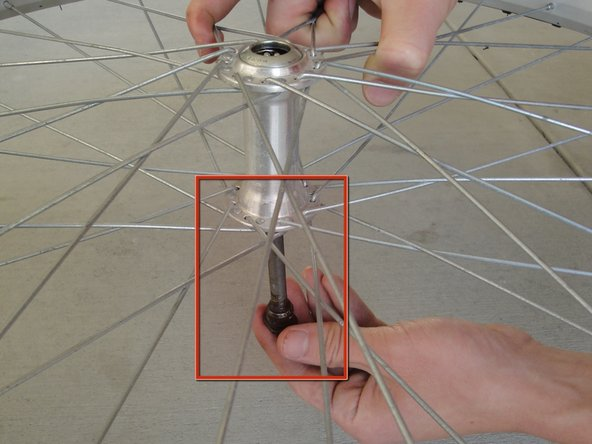 Carefully drop the axle out from the bottom of the wheel.