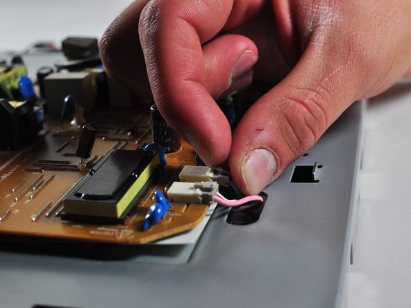 Remove the four plugs on the brown circuit board by pulling up on the tabs and wiggling them out. You could also use a spudger to help you lift little clips holding them in.