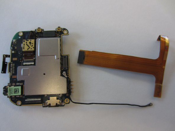 Noting that the rear side of the black ribbon cable is gold, use a spudger or an opening tool to gently disconnect it from the motherboard by levering it up at the right side
