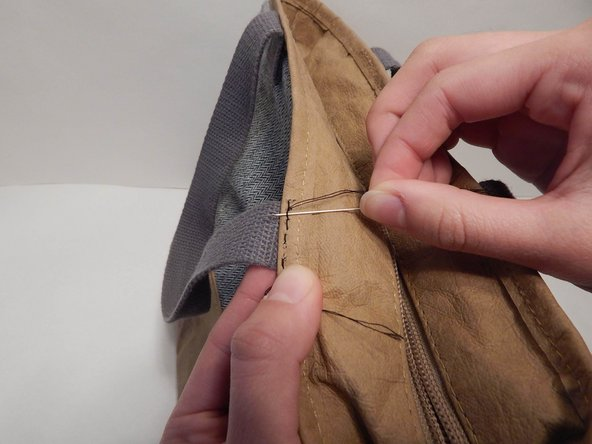 To end the last stitch, thread the needle between the lunchbox and thread of your last stitch. Rather than pulling the thread completely through, thread the needle back through the excess thread to make a knot.