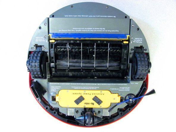 Lay the Roomba upside down on a flat surface.
