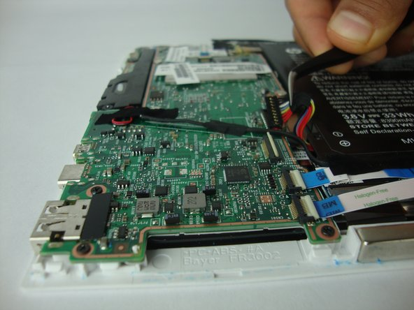 Remove the tape that covers the battery connector on the system board and carefully disconnect the battery cable from its connector on the system board.
