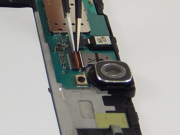 Use tweezers to lift the tab on the ZIF connector holding the ribbon cable in place.