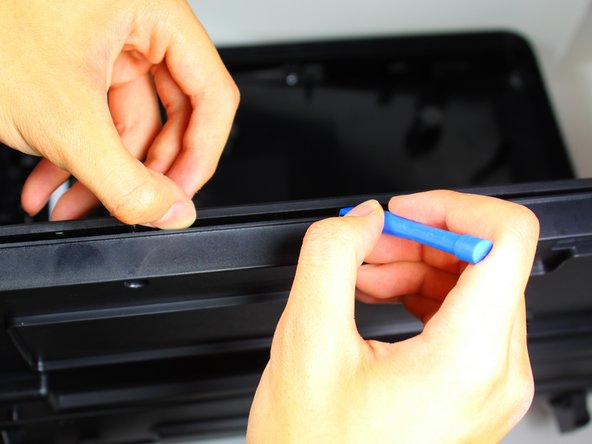 Wedge the plastic opening tool into the creases on the sides of the cartridge access door to help detach the glass side from the back side of the cartridge access door in the next steps.