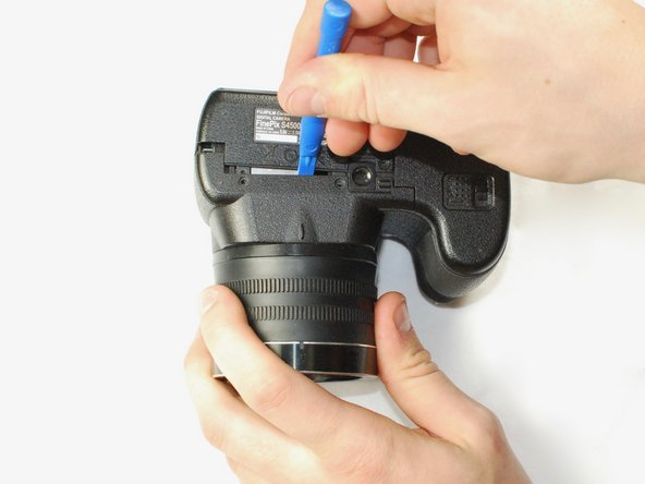 Use a plastic opening tool to separate the back panel from the camera on the bottom.