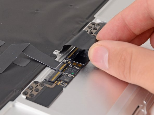 Image 1/3: Push/lift the keyboard ribbon cable off of the upper case with one hand.