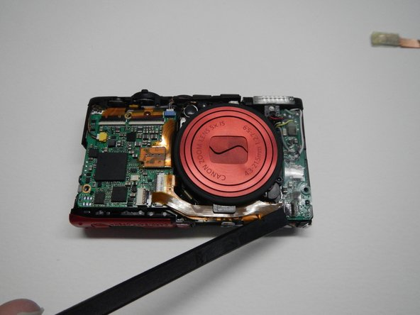 Remove the ribbon wire attached at the bottom right corner of the front of the camera.  You do NOT need to remove this from the motherboard.
