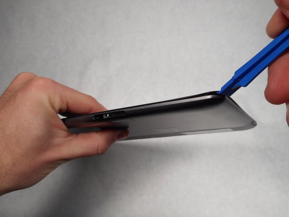 Use the plastic opening tool to help detach the screen from the back panel.