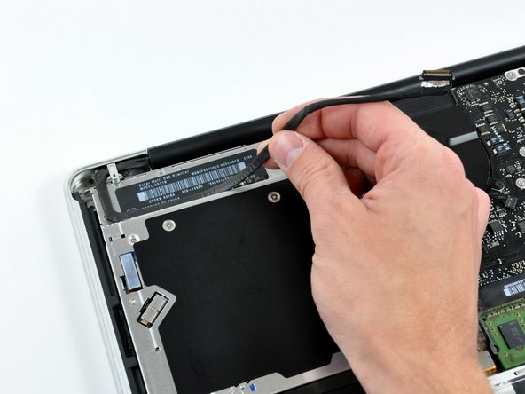 Disconnect the camera cable by pulling the male end straight away from its socket toward the optical drive opening.