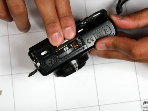 Rotate camera such that battery door is facing upwards
