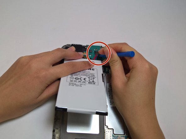 Use a plastic opening tool to remove the battery connector from its place on the motherboard. Make sure to pull it straight up.