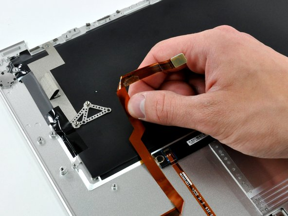 Peel the audio cable off the adhesive securing it to the upper case.
