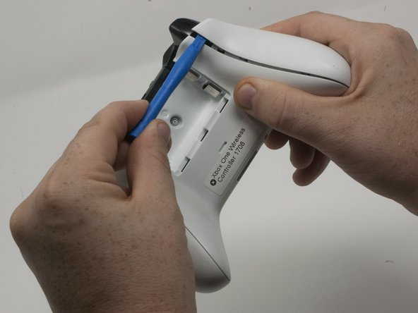 Insert a plastic opening tool into the top seam, and  gently work the opening tool to the bottom of the controller.