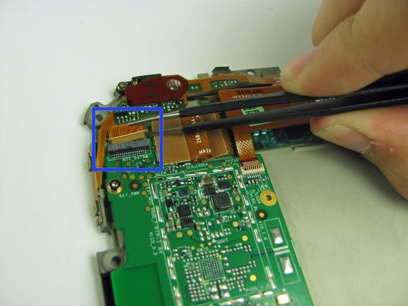 Image 2/2: Use the plastic opening tool to pull the black part of the ribbon cable housing up and away from the circuit board.