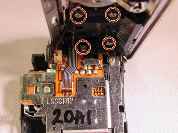 Unscrew the four silver 4 mm screws underneath the plastic outer cover to gain access to the bottom of the zoom lever.