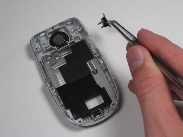 Using metal tweezers, lift out the black plastic support piece from beneath the headphone jack.