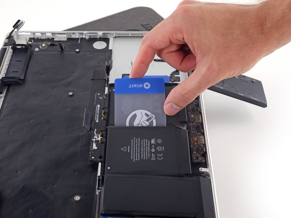 Don't try to fully separate this battery cell yet. Leave your plastic card in place to prevent it from re-adhering.