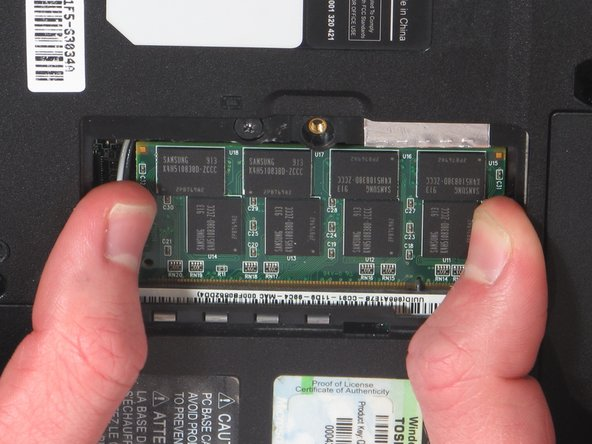 Image 1/2: Pull back the two silver clips that hold the RAM in place.