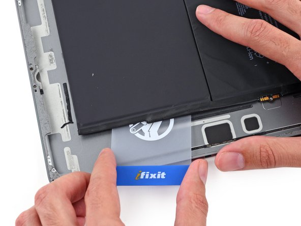 With the card roughly halfway inserted, slide it toward the top of the iPad, stopping before the battery contact post.