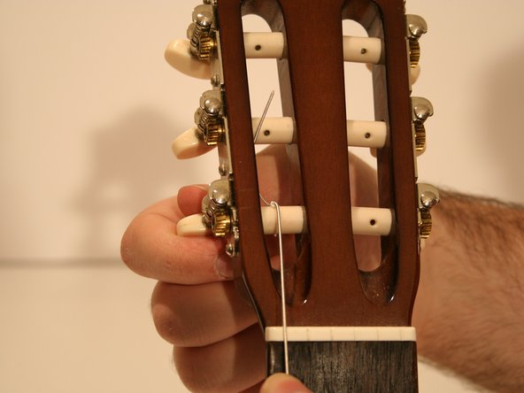 Turn the tuning knob in a clock-wise motion to tighten the string until the string makes a clear sound when plucked.