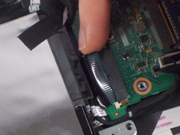 After the pins have been opened, detach the ribbon connector by gently pulling it out from the port.