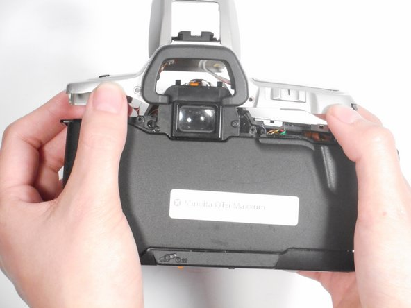 Once all screws are removed, lift the top panel from the camera.