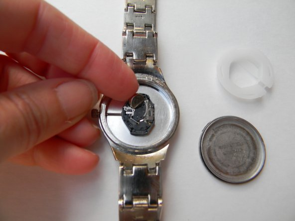 Put the new battery in watch. Use your fingers to insert the new battery.