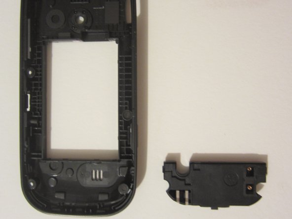 Use the TOOL to pry open the plastic piece located at the bottom of the rear case. This piece contains the speaker.
