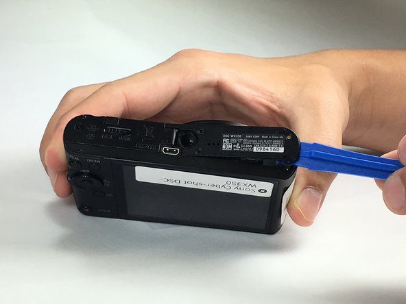 Using the plastic opening tool, carefully insert it between the camera cover and the bottom cover. Pull it apart.