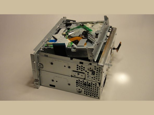 Lift the CD drive out of the unit, starting at the rear.