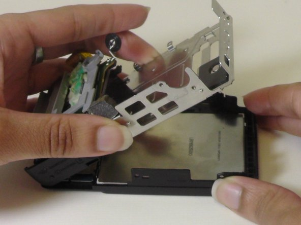 Flip the metal frame over to the left side of the camera and onto the surface on which you are working.