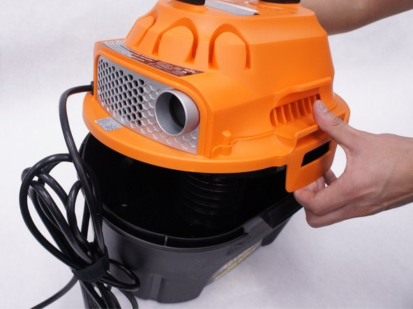Remove the orange main housing unit from the vacuum bucket by pulling outward on the handle tabs while lifting upward as shown.