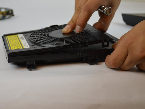 The latches are very thin and can break off easily so make sure to use caution when lifting them to remove the disk drive top.
