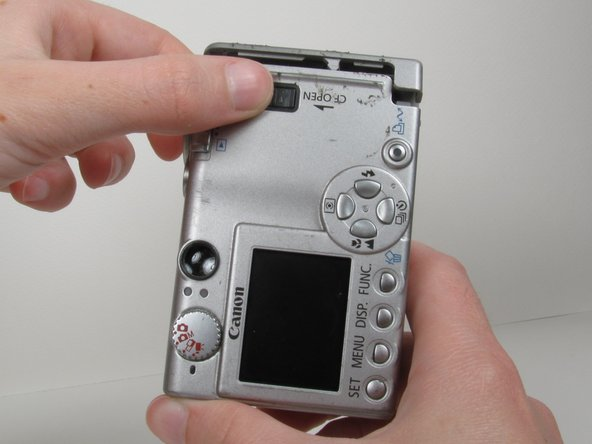 Open memory card cover by moving the slide switch toward the top end of of the camera.
