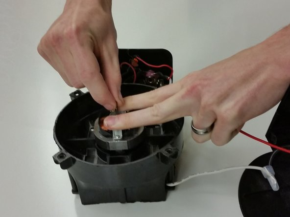 Push down on the motor bracket and adjust the motor by hand so it spins freely and does not scrape.